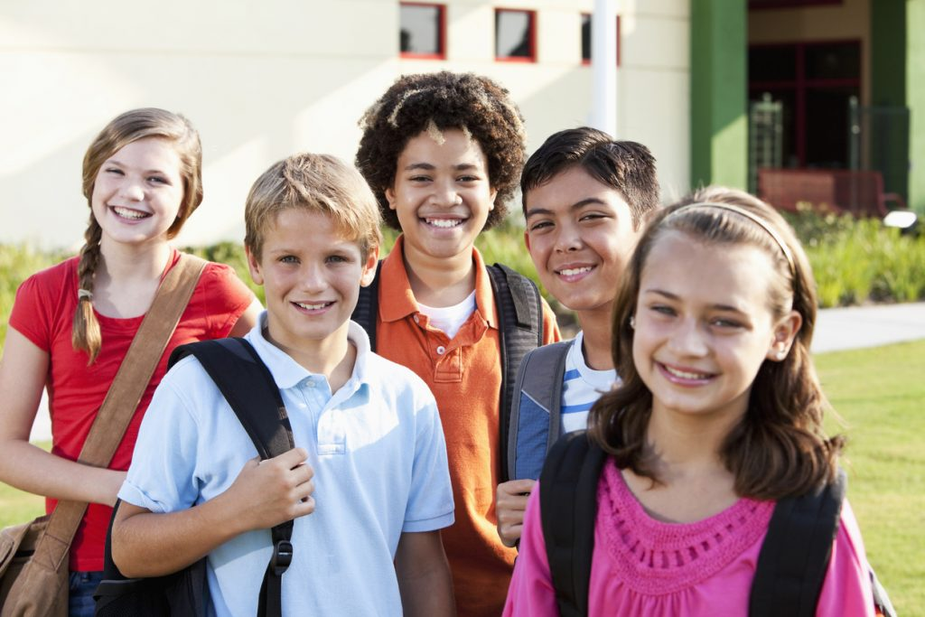 A multi-ethnic group of five elementary or middle school students standing outside a school building.  The focus is on the boys in the middle row.  The children are 10 to 12 years old.  They are smiling at the camera, all carrying bookbags or backpacks.  It is a bright, sunny day.